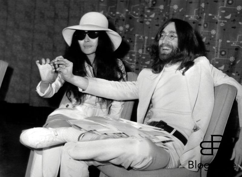 Beatle John Lennon and wife Yoko Ono after arriving at London Heathrow airport. They had been staying in bed for a week at the Hilton Hotel, Amsterdam as a protest against world violence. They are each holding a small acorn which they announced they are sending to each of the world